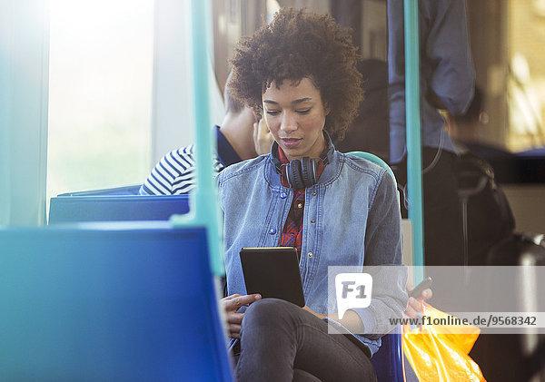 Frau mit digitalem Tablett im Zug