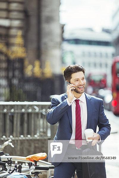 Geschäftsmann beim Telefonieren auf dem Bürgersteig der Stadt
