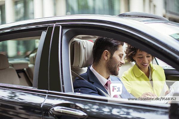 Geschäftsleute beim Lesen von Papierkram im Auto
