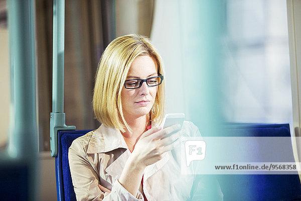 Geschäftsfrau mit Handy im Zug