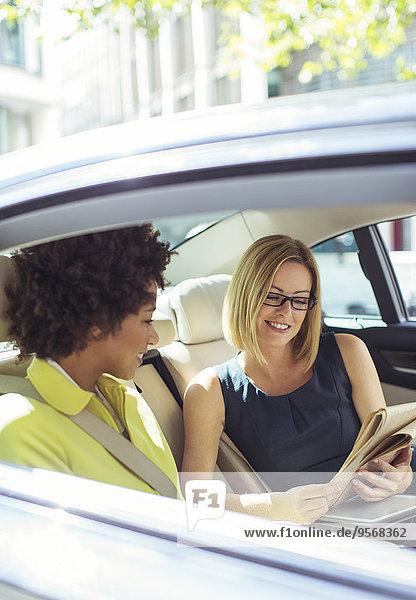 Geschäftsfrauen lesen Zeitung auf dem Rücksitz im Auto