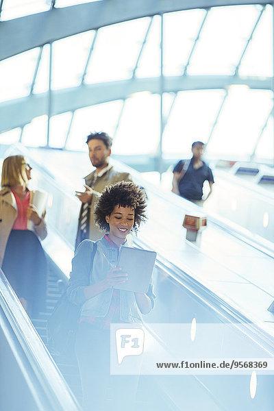 Frau mit digitalem Tablett auf der Rolltreppe