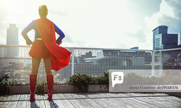 Superheld steht auf dem Dach der Stadt