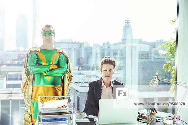 Superheldin in der Nähe einer Geschäftsfrau  die im Büro arbeitet.