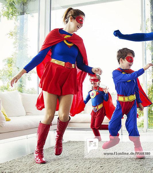 Familie der Superhelden beim Spielen im Wohnzimmer