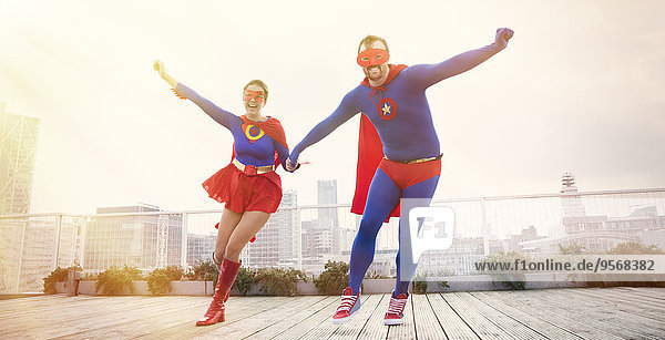 Superhelden  die auf dem Dach der Stadt Händchen halten.