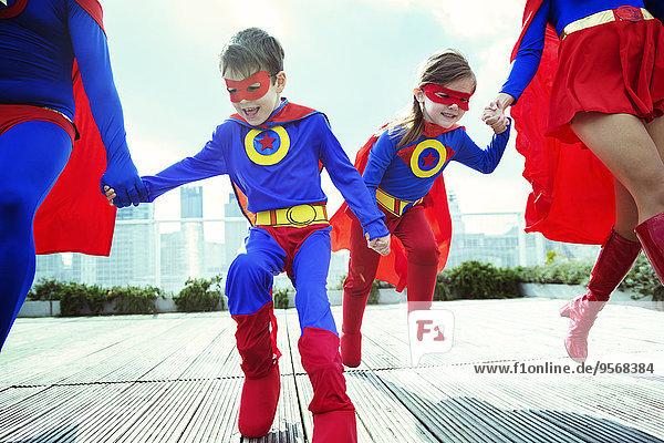 Familie der Superhelden auf dem Dach der Stadt
