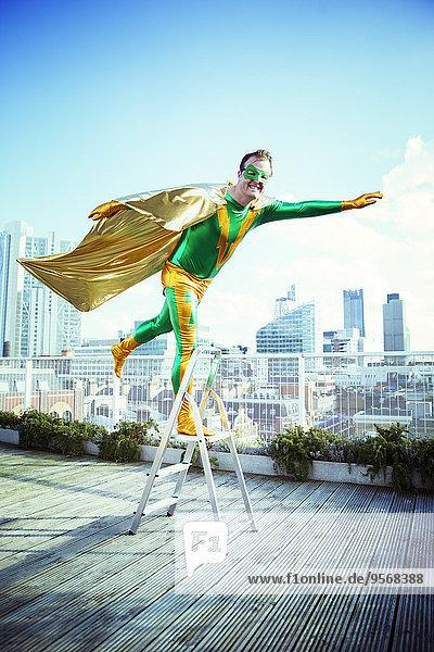 Superheld posiert auf der Stufenleiter auf dem Stadtdach