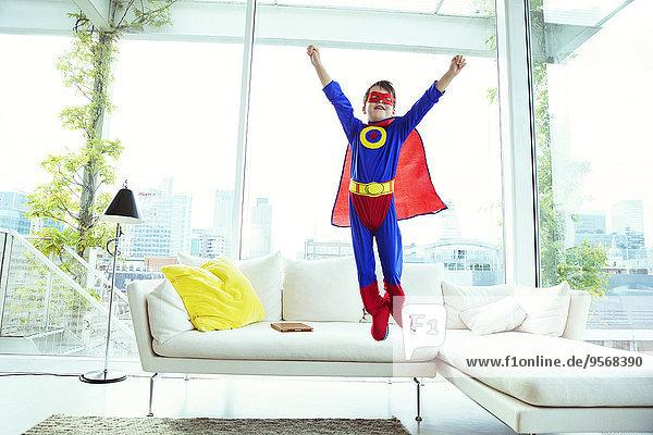 Junge Superheld springt vom Wohnzimmersofa