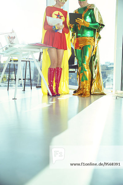 Superheld Geschäftsleute lesen digitales Tablett im Büro