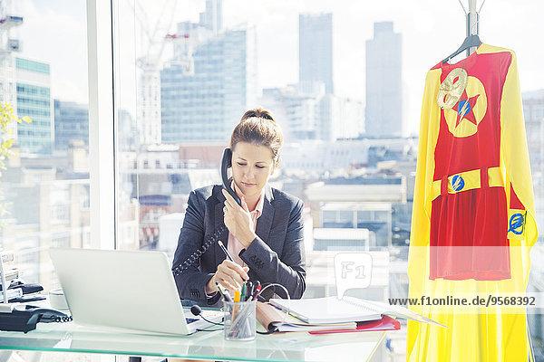 Geschäftsfrau bei der Arbeit mit Superheldenkostüm im Büro