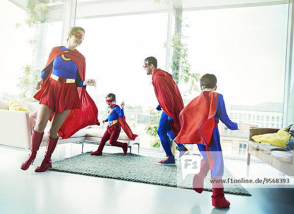 Superheldenfamilie jagt sich im Wohnzimmer hinterher