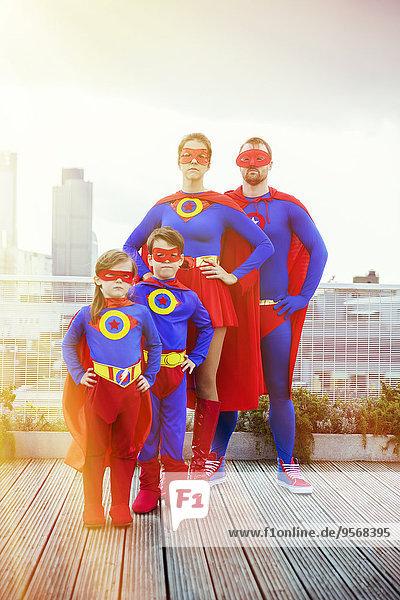 Superheldenfamilie steht auf dem Stadtdach
