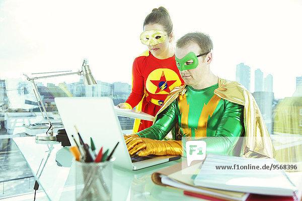 Superhelden bei der Arbeit mit dem Laptop im Büro