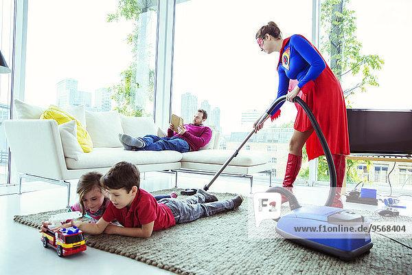 Superhelden saugen im Wohnzimmer um die Familie herum