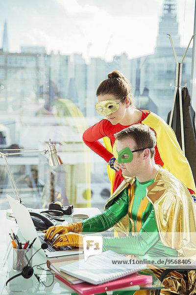 Superhelden bei der Arbeit am Laptop im Büro