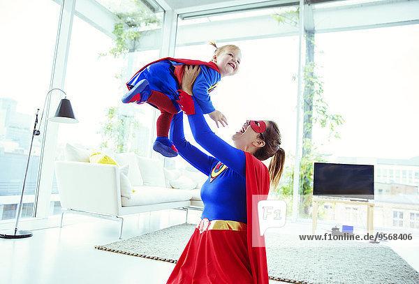 Superheld spielt mit Baby im Wohnzimmer