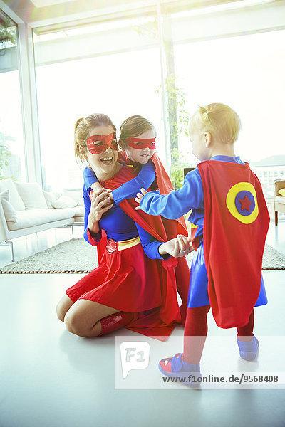 Superheldenmutter und Kinder beim Spielen im Wohnzimmer