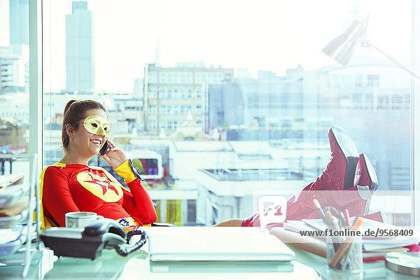 Superheld spricht am Schreibtisch auf dem Handy