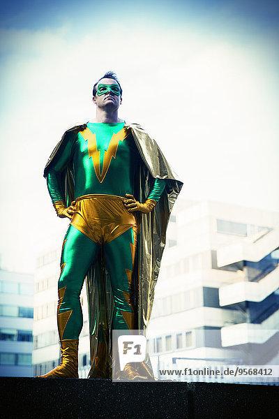 Superheld steht in der Nähe der Skyline der Stadt