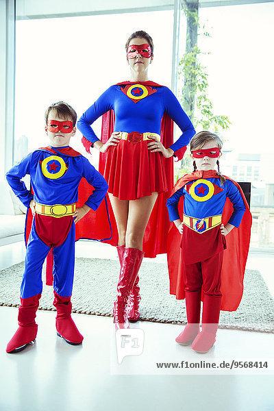 Superheldenmutter und Kinder im Wohnzimmer stehend