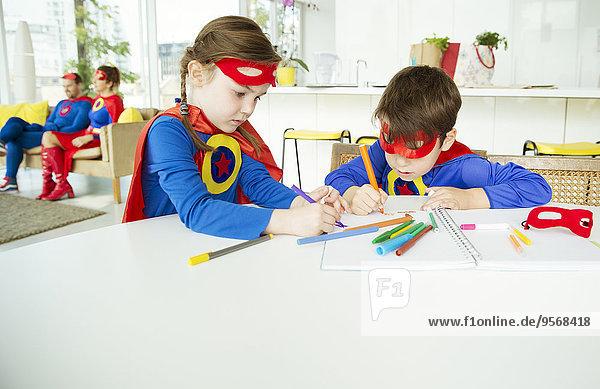Superheldenkinder beim Zeichnen am Tisch