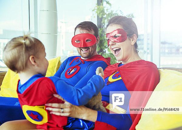 Superhelden-Eltern spielen mit Tochter auf dem Wohnzimmersofa