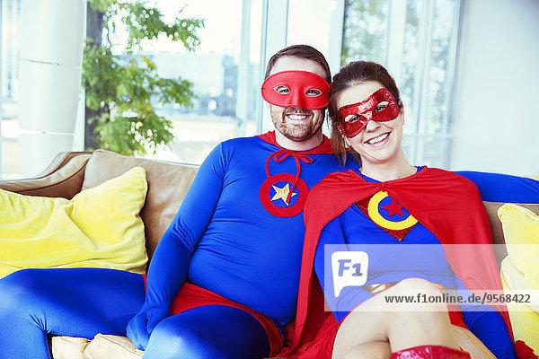 Superheldenpaar lächelt auf Wohnzimmersofa