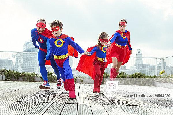 Superheldenfamilie spielt auf dem Stadtdach
