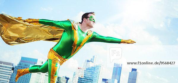 Superheld fliegt auf dem Stadtdach