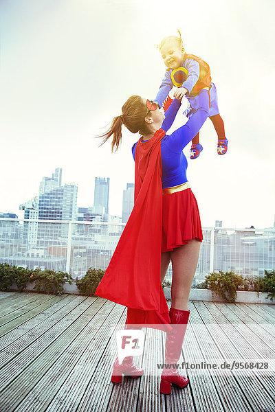 Superheldenmutter spielt mit Tochter auf dem Stadtdach