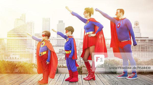 Superheldenfamilie steht mit ausgestreckten Armen auf dem Stadtdach