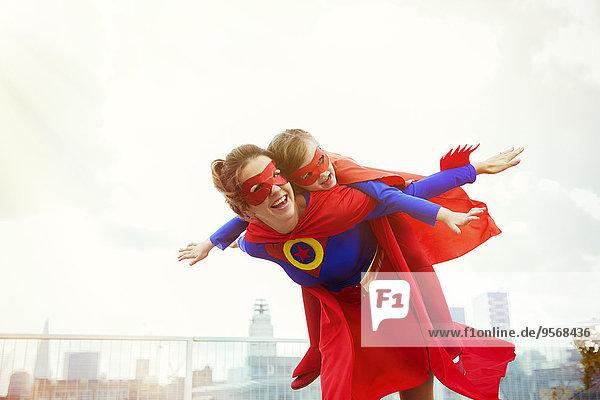 Superhelden-Mutter und -Tochter spielen auf dem Dach der Stadt