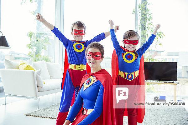 Superheldenkinder und Mutter lächeln im Wohnzimmer