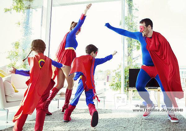 Superheldenfamilie beim Spielen im Wohnzimmer