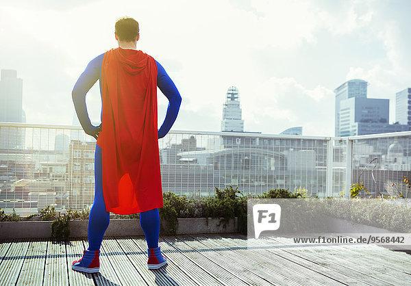 Superheld mit Blick vom Stadtdach aus