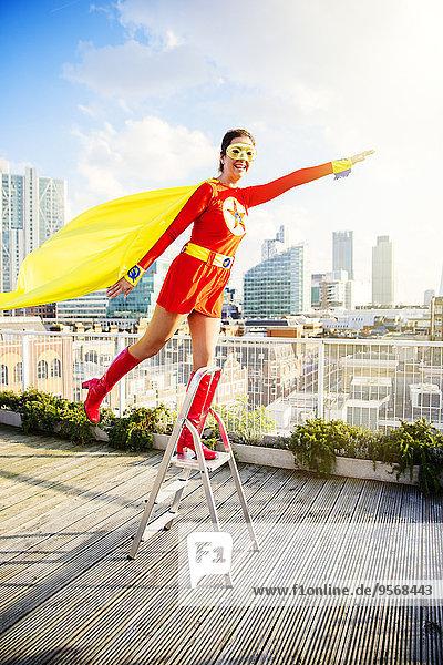 Superheld steht auf Stufenleiter auf dem Stadtdach