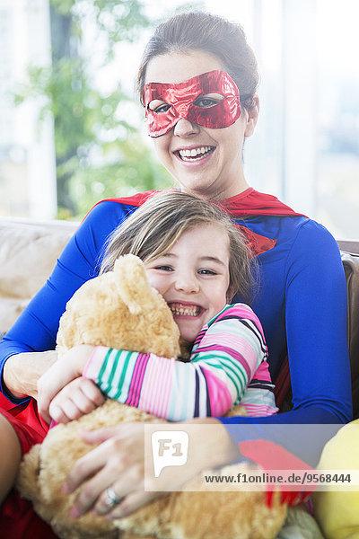 Superheldenmutter umarmt Tochter auf Sofa
