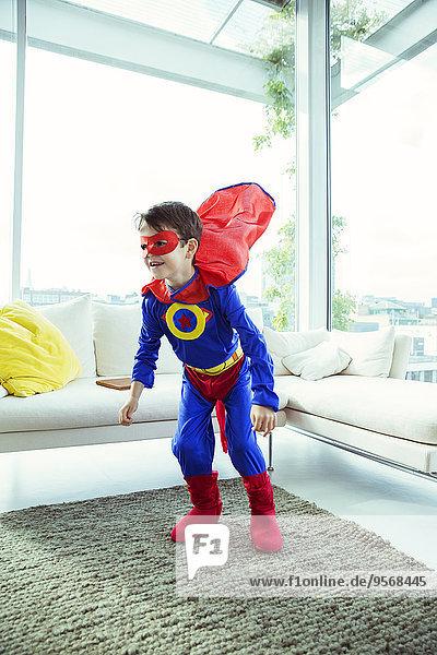 Superheldenjunge spielt im Wohnzimmer