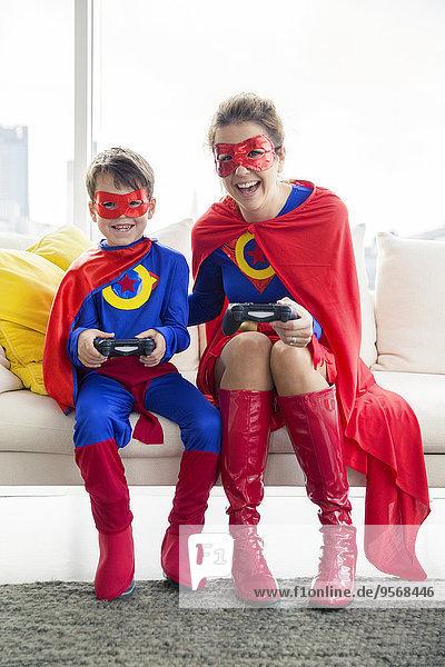 Superheld Mutter und Sohn beim Videospiel im Wohnzimmer
