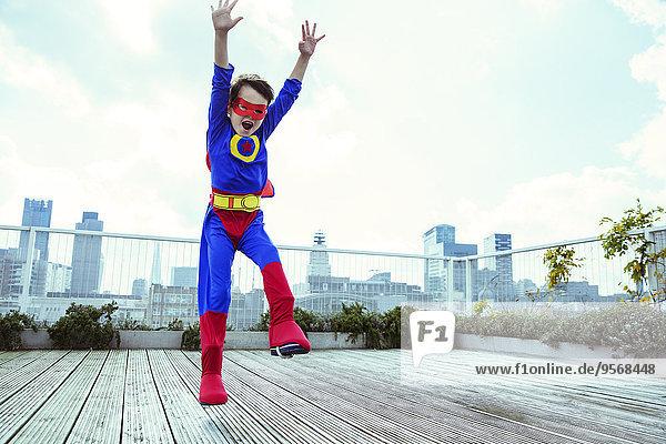 Superheldenjunge springt auf das Stadtdach