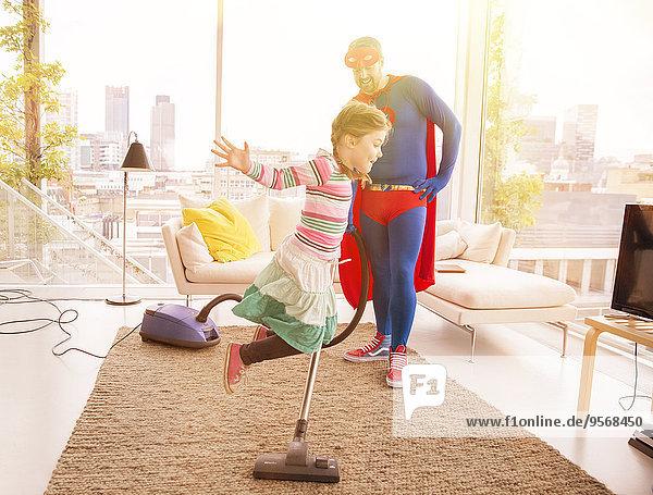 Superhelden-Vater beim Staubsaugen  während die Tochter im Wohnzimmer springt.