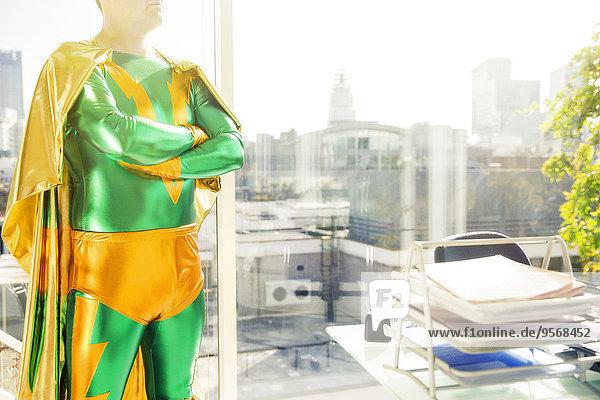 Superheld steht neben Schreibtisch