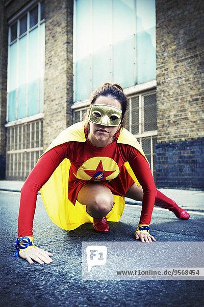 Superheld kauernd auf der Stadtstraße