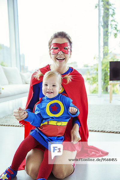 Superheld umarmende Tochter auf dem Wohnzimmerboden