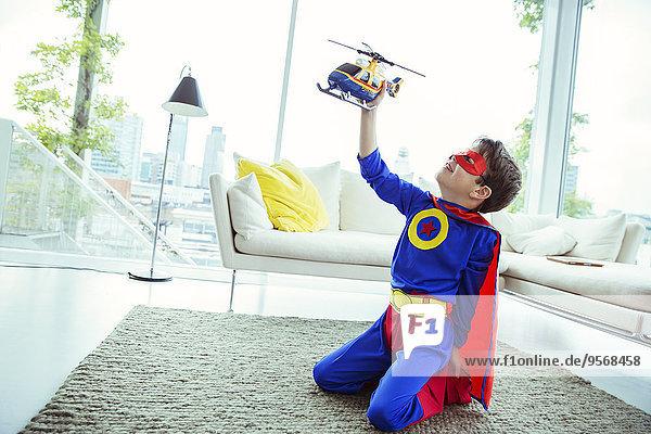Superheldenjunge spielt mit Spielzeughubschrauber im Wohnzimmer