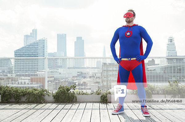 Superheld stehend mit den Händen auf dem Dach der Stadt