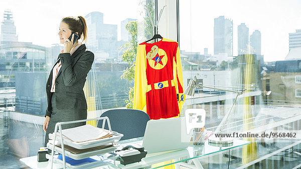Geschäftsfrau spricht am Handy mit einem Superheldenkostüm hinter sich.