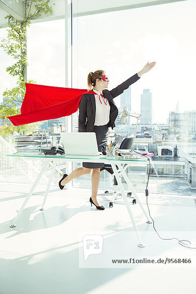 Geschäftsfrau  die sich auf das Fliegen mit Umhang und Maske im Büro vorbereitet.