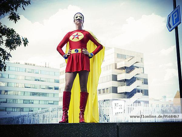 Superheld stehend mit den Händen auf den Hüften in der Stadt